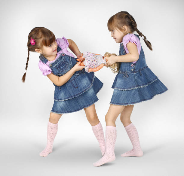 little twin girls fighting and shared doll stock photo