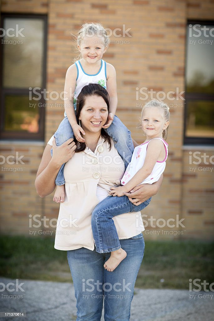 Little Twin Girls Standing With Mom Outside Brick Building stock photo