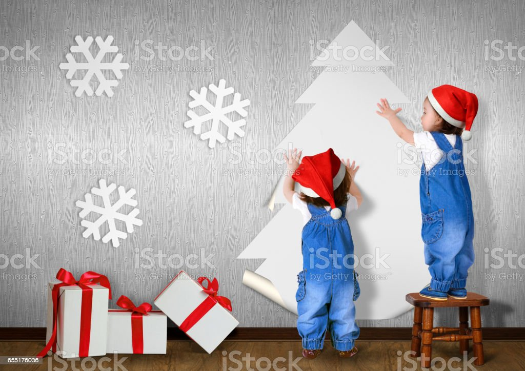 Little twins dressed Santa hat, glue Christmas tree on wall at home, xmas concept stock photo