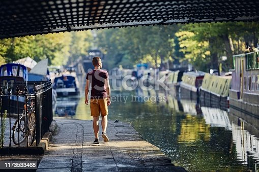 Young man walking on waterfront of Regents canal with boats. Little Venice in London, United Kingdom.