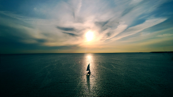 Little white boat floating on the water towards the horizon in the rays of the setting sun. Beautiful clouds with yellow highlights. Aerial view