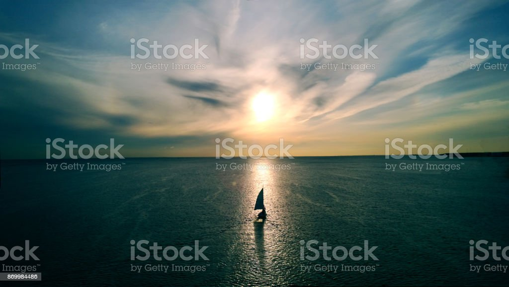 Little white boat floating on the water towards the horizon in the rays of the setting sun. Beautiful clouds with yellow highlights. Aerial view - foto stock