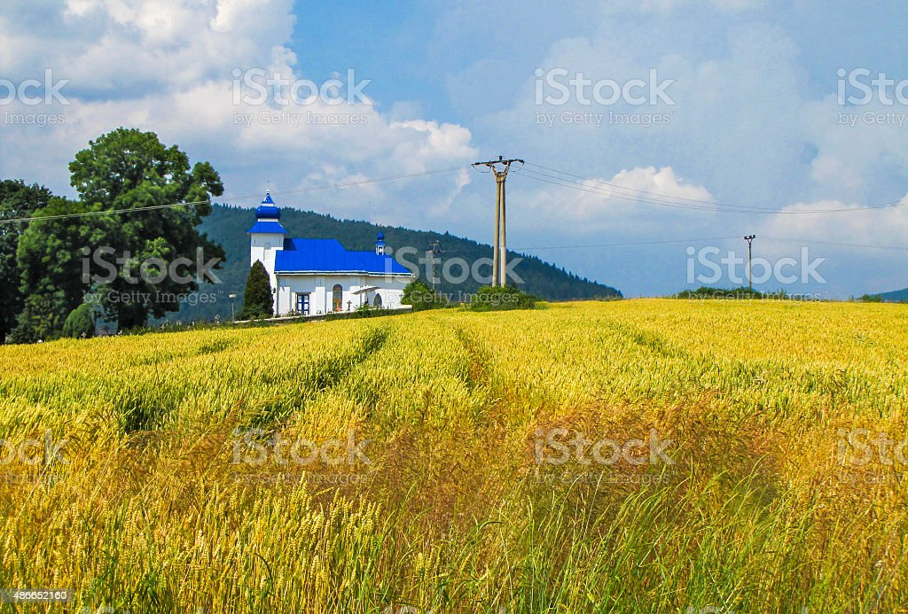 Little white church with blue roof in Poland stock photo