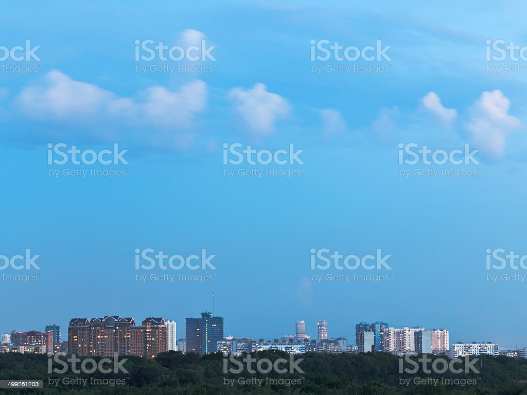 little white clouds in blue dusk sky over city royalty-free stock photo