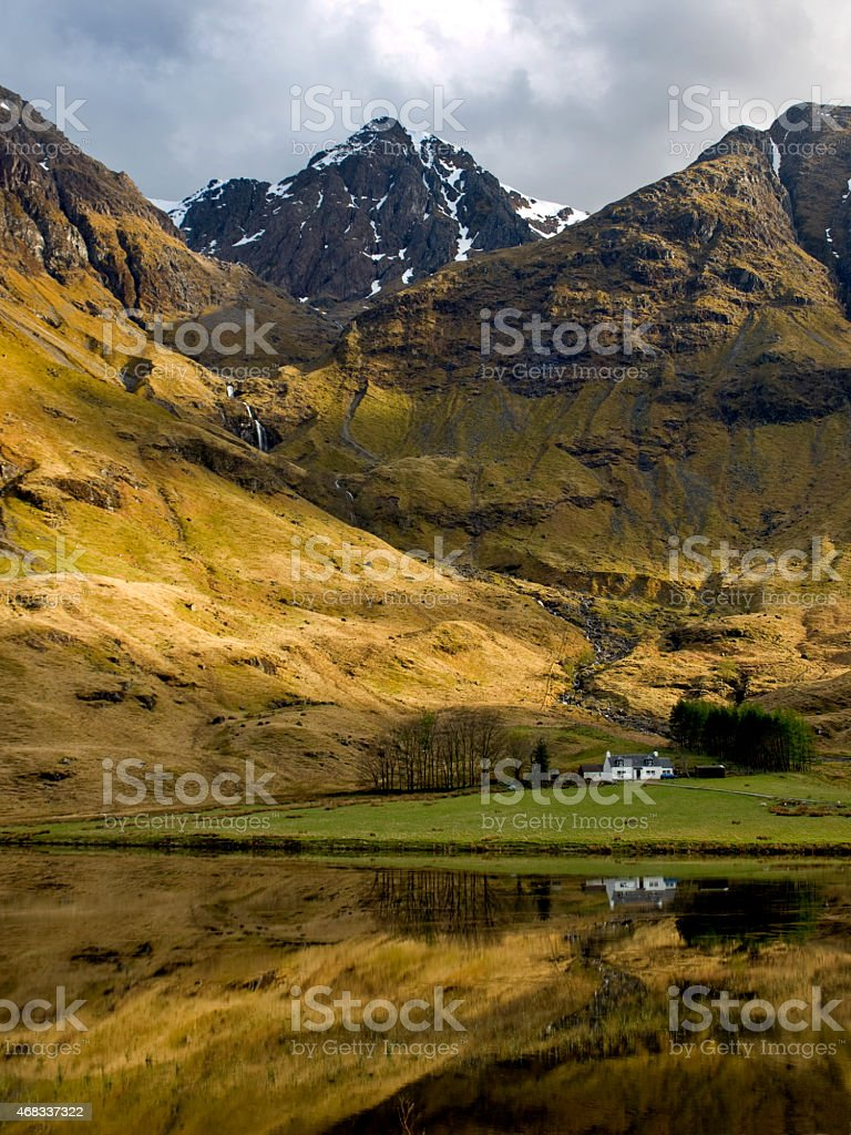Little white cottage amongst mountains by a lake. stock photo