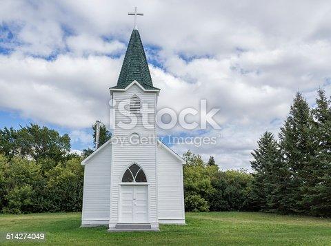 horizontal image of a quaint little white country church with a steeple sitting in a green meadow surrounded by trees under a beautiful blue sky with white clouds floating by in the summer time.