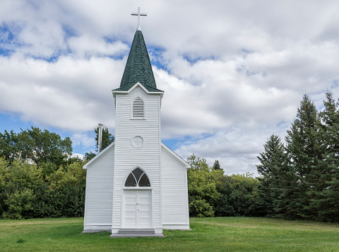 little white country church with steeple surrounded by green trees.