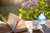 istock Little white cup of espresso coffee, opened book, blue semi-transparent vase with purple lilac flowers on rustic wooden table in the garden at spring morning after sunrise or at evening before sunset 1240431130