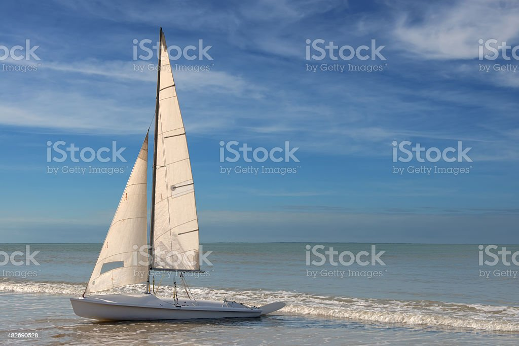 little white sailboat grounded on a beach stock photo