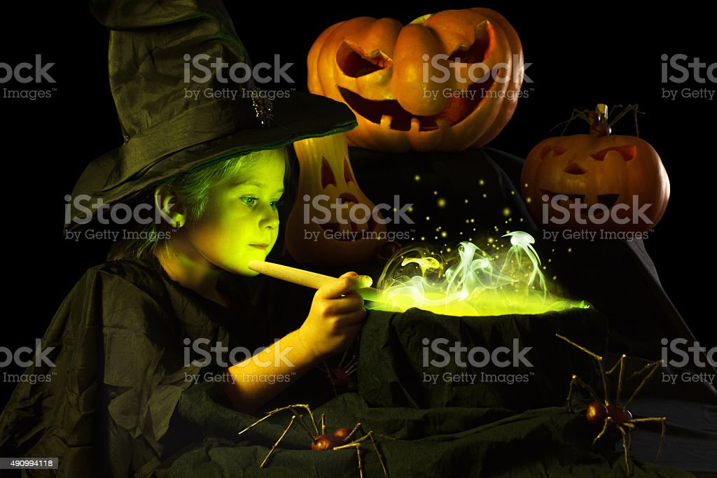Little witch cooks a magic potion on Halloween stock photo