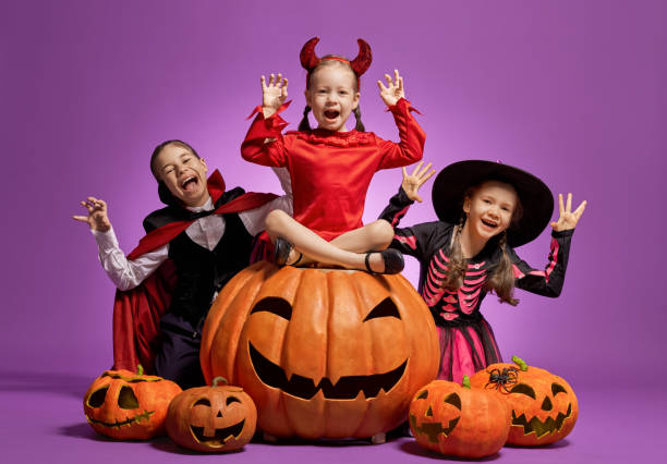 little witch, Dracula and pumpkin on purple background stock photo