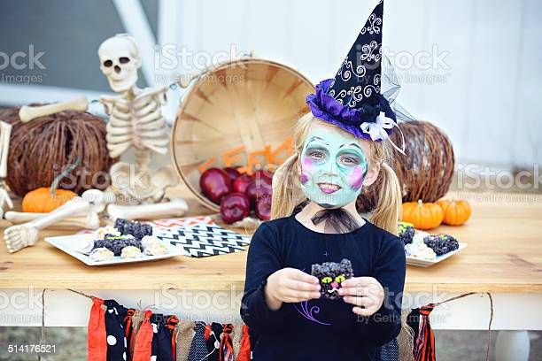 Little witch holding cookie in front of halloween table picture id514176521?b=1&k=6&m=514176521&s=612x612&h=4fotdmphxg9g4xtthonz3m0xx1zjkgv68fzvkftdvo0=