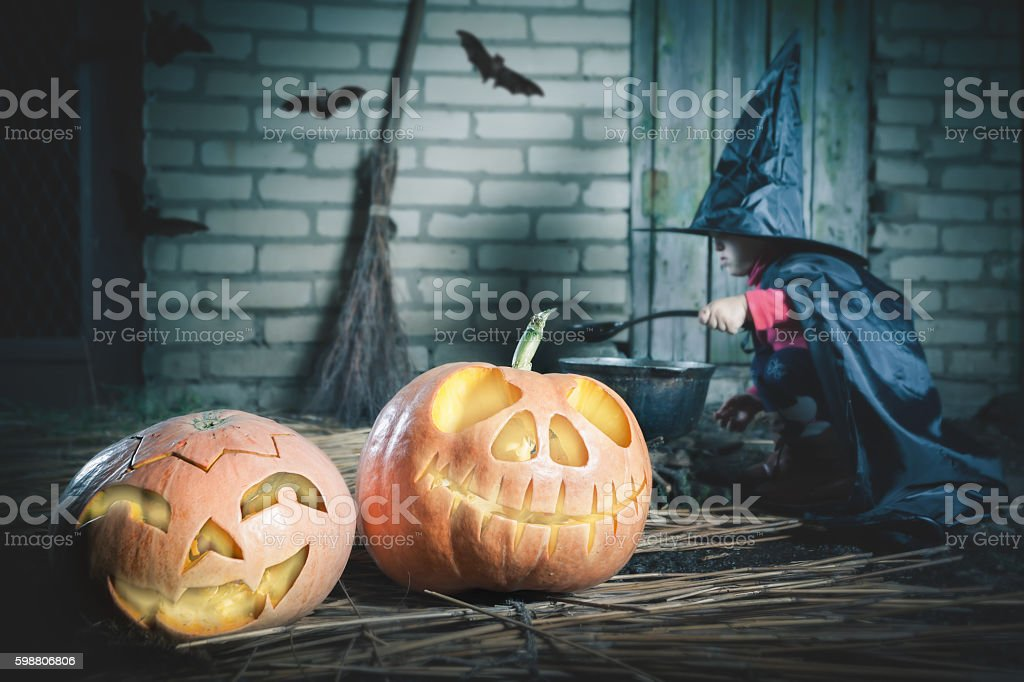 Little witch making a magic potion at Halloween night. Pumpkin. stock photo