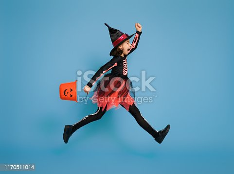 Happy Halloween! Cute little witch with a pumpkin on blue background.