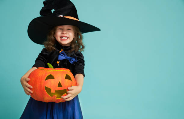 little witch on turquoise background stock photo