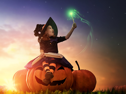 Happy Halloween! Cute cheerful little witch with a magic wand and book of spells. Beautiful child girl in witch costume sitting on the big pumpkin, conjuring and laughing.