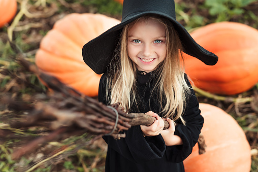 Cute little witch with a broom. Halloween theme.