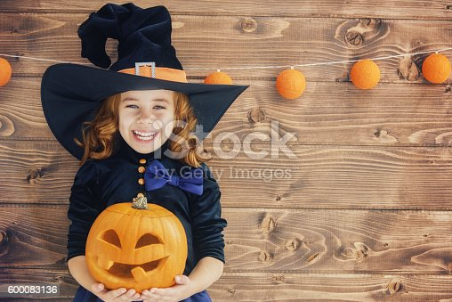istock little witch with a pumpkin 600083136