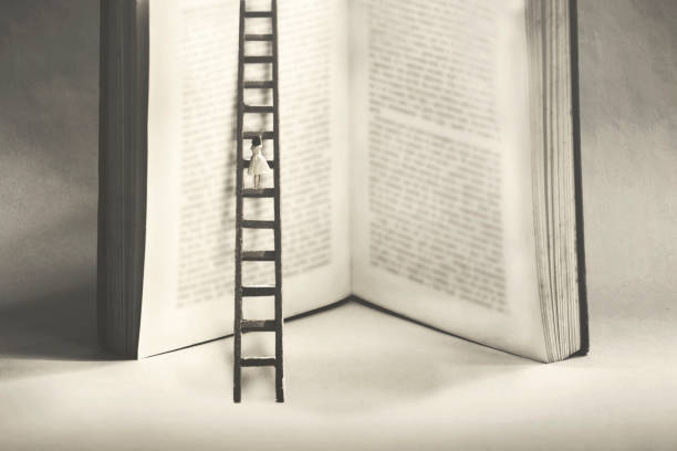little woman tries to reach the summit of knowledge by climbing a gigantic book stock photo