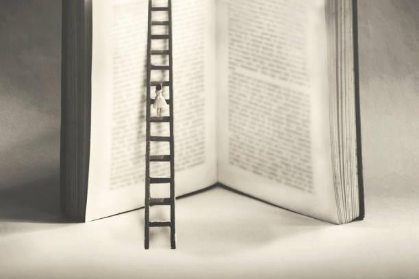 kleine Frau versucht, den Gipfel des Wissens zu erreichen, indem sie ein gigantisches Buch erklimmen – Foto