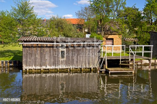 Priepert, Germany - May 3, 2014: Little wooden Boats House in the village Priepert in the Mecklenburg Lake District. In these shelters are housed little boats and ships or rowing boat. Seen is also a wooden jetty and in background other buildings.