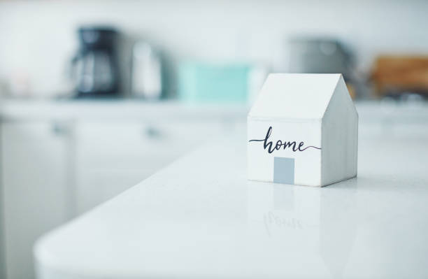 Little wooden home in bright white kitchen. New home concept. stock photo