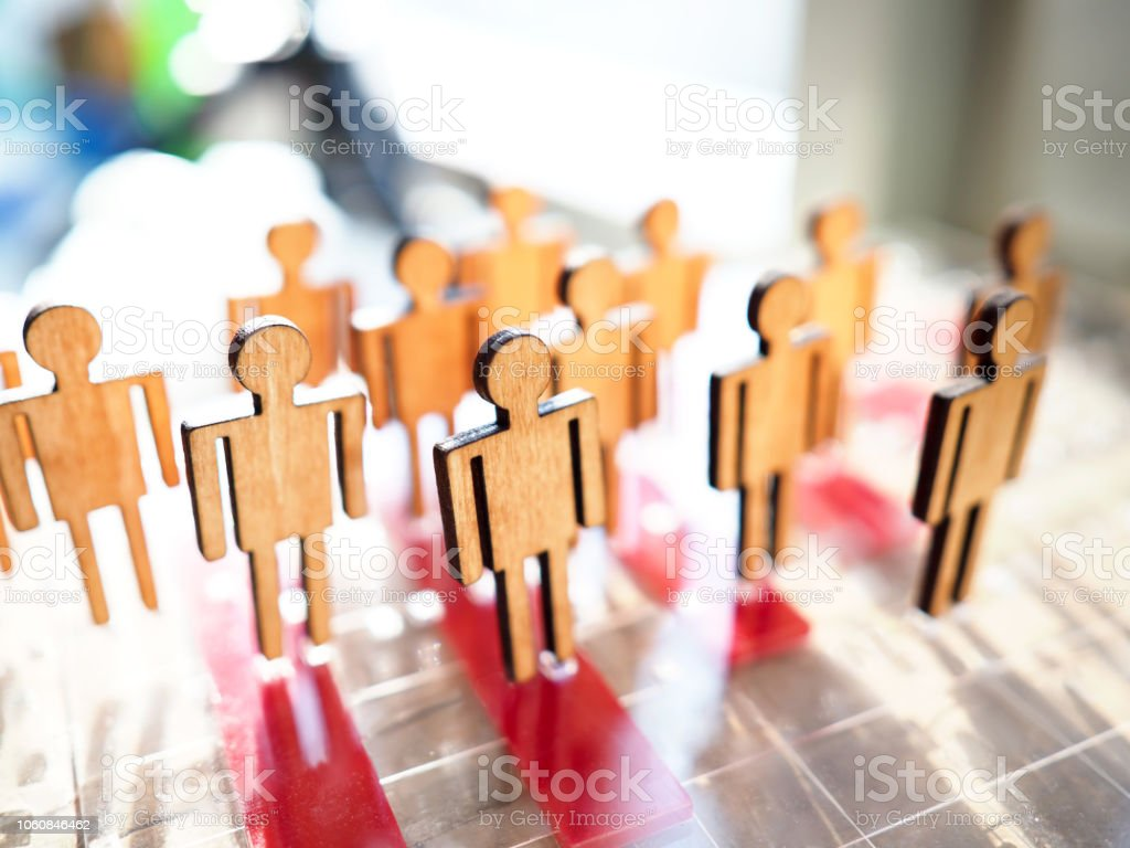 Little wooden toy people figures stand in row stock photo