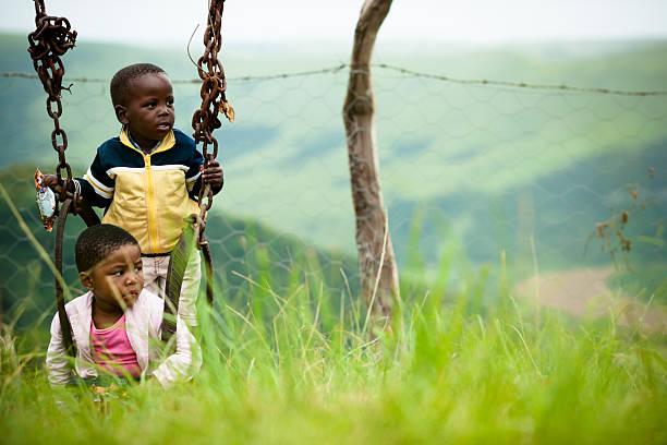 Little Xhosa girl and boy sitting in swing stock photo
