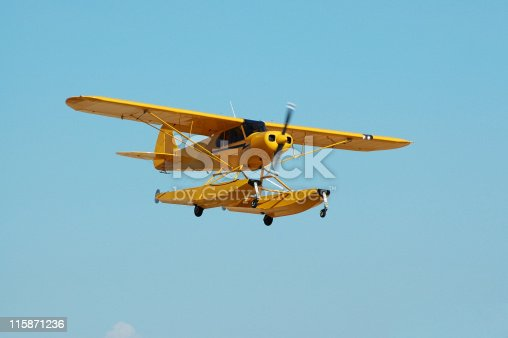 Little yellow seaplane with floats or pontoons for landing on water. Common bush plane in Canada and Alaska. Piper Cub.