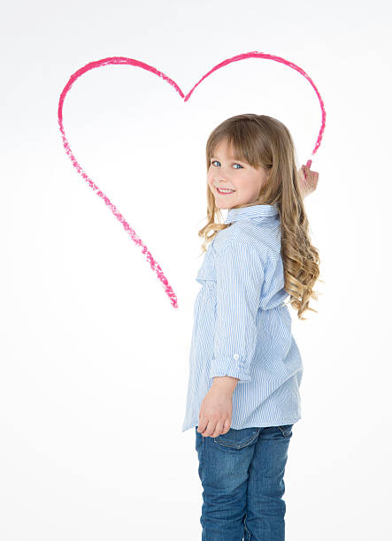little young child drawing big heart stock photo