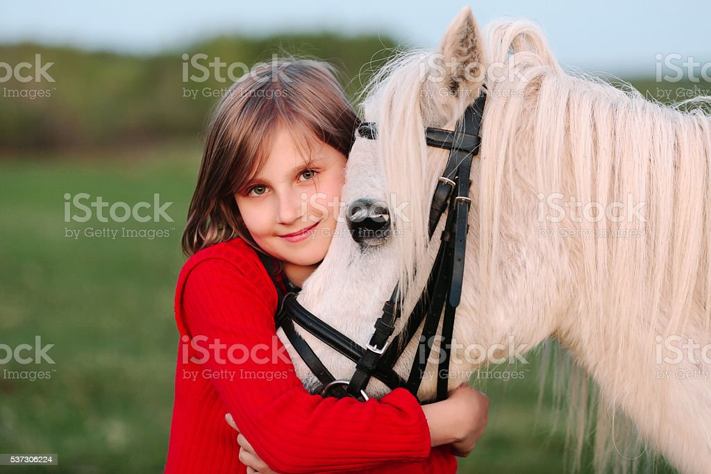 Little young girl red dress hugging his head white horse stock photo