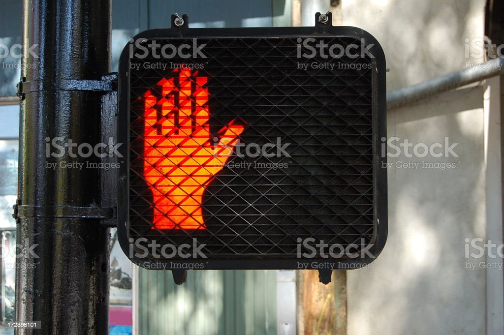 A lit-up red hand sign indicating not to walk on crossings stock photo