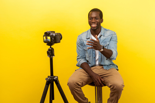 Live blog. Portrait of positive friendly happy man smiling at his professional dslr camera. isolated on yellow background