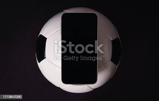 843298172 istock photo Live football betting concept, online broadcast, blank smartphone display on classic soccer ball isolated on black background. Sports gambling copy space app, play entertaining games on mobile phone. 1213642050