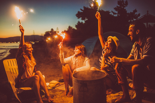 Couple of smiling friends at the beach, celebrating their friendship and life - by holding a torches  up high