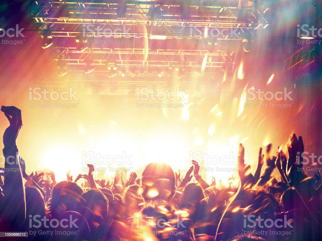Concert spectators in front of a bright stage with live music