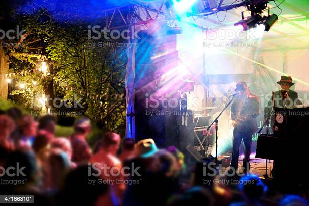 A band perform in front of festival go-ers at an outdoor live music festival, Castlewood Wine Festival, Devon
