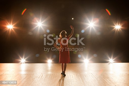 Live performer standing on a stage with bright lights.