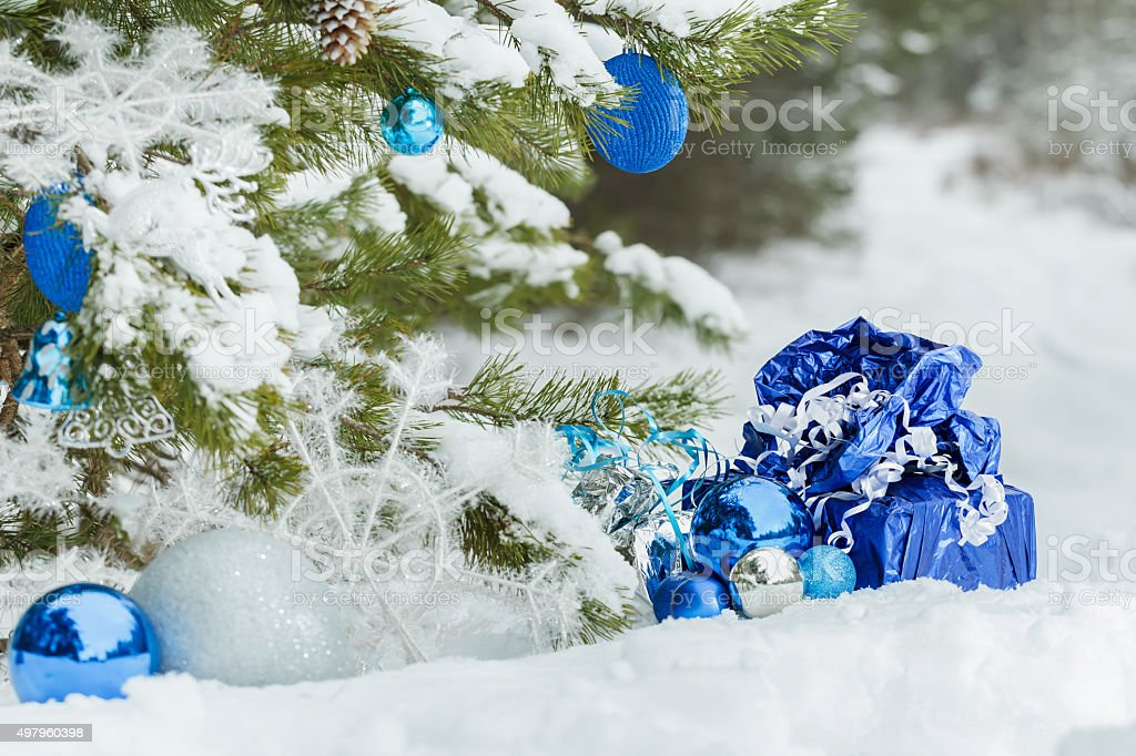 Live pine tree decorated with Christmas ornaments and wrapped presents stock photo