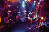 A rock band plays a live performance in a small club in Tokyo, Japan.