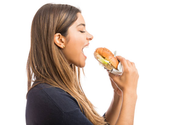 I Live To Eat Side view of attractive woman following unhealthful diet on white background mouth open stock pictures, royalty-free photos & images