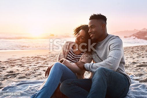 Shot of a happy young couple relaxing on a blanket during sunset at the beach