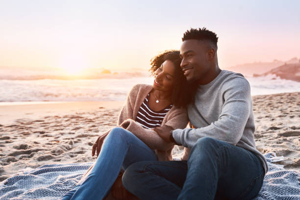 Live where the sun meets the ocean Shot of a happy young couple relaxing on a blanket during sunset at the beach romantic activity stock pictures, royalty-free photos & images