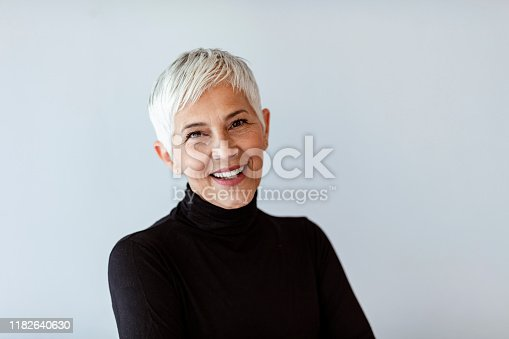 Casual portrait of happy mature woman with natural white short hair and minimal makeup. standing against gray wall.