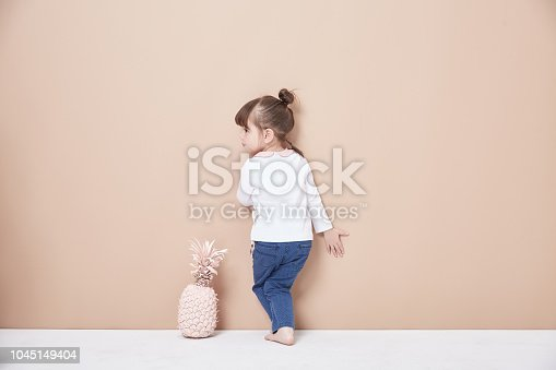 istock A lively and cheerful girl, dressed in jeans and white, smiled innocently. 1045149404