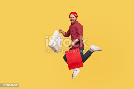 Lively happy hipster trendy guy running in air with shopping bags in hands, hurrying to catch sale, flying and rushing for thrift discount. full length studio shot isolated on yellow background