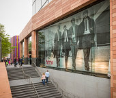Liverpool, UK - May 18, 2013: A large format poster of The Beatles in the window of an HMV shop in central Liverpool, with people walking on the stairs below and the street.