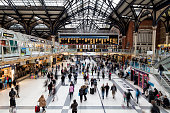 Main entrance hall of Liverpool Street train station in London, UK. People are rushing by, train destinations are shown on the arrival/departure board. Liverpool Street station serves as a major train and subway hub in the East of the City of London, horizontal orientation, England, UK.