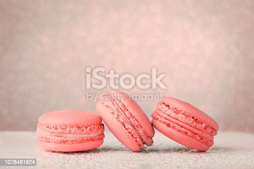 istock Living Coral color of the Year 2019 Macarons on glitter bokeh background. 1078481624