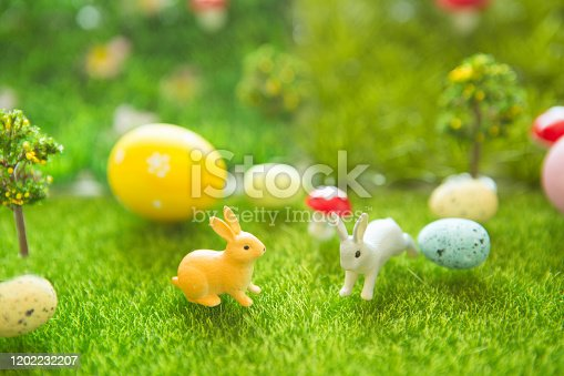 Living Easter bunny with easter eggs on a meadow in spring of Dreamland or fairy world.